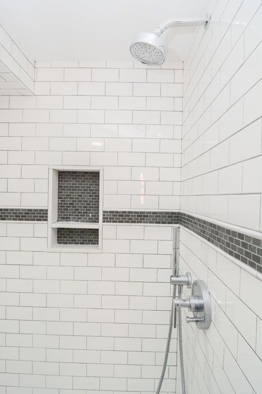 The basement guest suite features a walk-in glass shower with classic subway tile with marble accents.